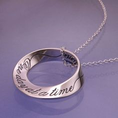 "A beautiful reminder of the need to live for this day, the inscription on this sterling silver mobius twist necklace simply reminds us to take things ""One day at a time"". The engraved message on the m"