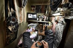 "In Hong Kong around residents live in what are being called ""coffin homes."" In this image a resident eats a tin of beans while watching TV in his single-mattress-sized flat, c. Photo credit: Benny Lam — in Hong Kong."