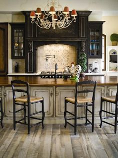This black cabinetry is accented with gray heavily distressed island and light reclaimed looking wood floors to create an old world look, Habersham
