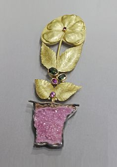 """Pink Flower Pot  Two-part brooch. Top: 14k gold, with pink & green sapphires. Bottom: 14k gold, with 18pt pink sapphire, and cobalto calcite druse. Mounted and framed. Approx 3 1/2 x 1 1/4""""."""
