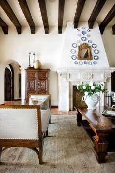 SPANISH: This style has contrast between wood beams, white plaster walls, and often terracotta tile (sometimes dark wood floors). Spanish homes are colorful with decorative tile. Leather, ironwork, and arches are distinguishing elements. Stone fireplaces slope in as the go up towards the ceiling.