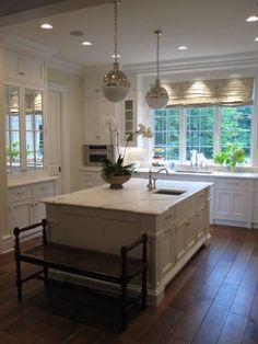 source: Phoebe Howard  Stunning U shaped kitchen design with Thomas O'Brien Hicks Pendants - mirrored uppers