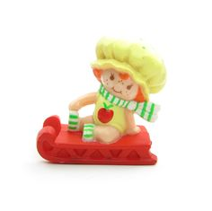 """This vintage Strawberryland Miniatures figurine is """"Apple Dumplin on a Sled."""" Apple Dumplin is a friend of Strawberry Shortcake and is sitting on a red sled or toboggan. She's wearing her classic yell"""