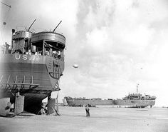 These tow American landing craft set high and dry on the beach of the Normandy coast of France on June 1944 as unloading operations continue while crewmen await return of the tide to refloat them. Unneeded anchor hanging from stern of craft at left. Battle Of Normandy, D Day Normandy, Normandy Invasion, D Day Landings, Landing Craft, History Online, Military History, World War Two, Wwii
