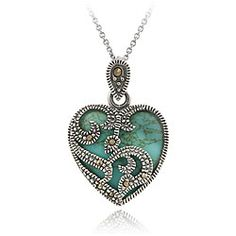This heart-shaped turquoise pendant showcases a floral overlay design dotted with marcasite stones. The necklace is crafted of sterling silver with rhodium plating and an antiqued finish.