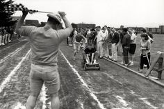Black and white photo of University of Oregon students participating in a pushcart race at Hayward Field in 1964. Nearing the finish line is the winning entry ridden by Scott Taylor and pushed by his brother. ©University of Oregon Libraries - Special Collections and University Archives