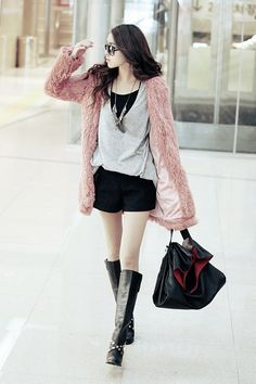 Love the fluffy coat and knee high boots combo. Admire her guts to make it work!