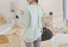 Mint green long sleeve top with a white blouse underneath and light gray skinny jeans