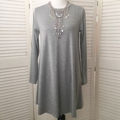 Long sleeve grey stretch knit swing dress So cute and flirty! Lightweight knit in a lovely pale grey. Perfect amount of stretch. Scoop neck, long sleeves. No size tag, but in my opinion, will fit a small best. (Dress form is a size 4, for reference.) NWT; never even tried on. Dresses Long Sleeve