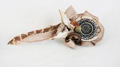 TOCADO Y BROCHE RUTAS SALVAJES Descubre tu lado más salvaje con este original y delicado accesorio. Mandala de cuero vacuno reciclado, estampado a mano con tinta permanente libre de ácidos. Doble orla de seda y lino en tono natural cosidos a mano. Pluma de ave real, bellota y eucalipto, perforados a mano y ensamblados con alambre.  Base metálica de doble función: broche y pinza para el pelo. 64€