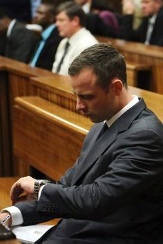 For those following this case. Oscar Pistorius looks at his watch as the start of his trial is delayed