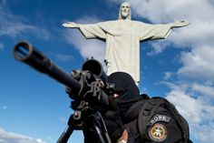 Members of the Elite Unit of the Brazilian Military Police (BOPE) practice maneuvers in front of the Christ the Reedemer statue on Corcovado Hill in Rio de Janeiro, Brazil, on April 6, 2013. Rio de Janeiro will host matches of the FIFA Confederation Cup in June and the 2013 World Youth Day international Catholic gathering in July