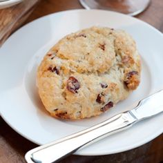Add cranberries, stirring to combine. Set aside.  • In a small bowl, combine milk and 1 beaten egg, stirring  well. Add to flour mixture, stirring just until combined. Turn  dough out onto a floured surface, and knead gently 6 to 8  times. Roll dough to a ¾-inch thickness. Using a 2½-inch  round cutter, cut scones from dough. Brush scones with  remaining beaten egg, and sprinkle with turbinado sugar.  • Bake until edges are golden brown, 10 to 12 minutes.