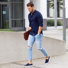 a navy shirt, ripped jeans and navy slip ons