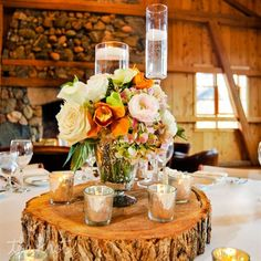 Rustic vases filled with roses and orchids topped tree stump stands. Mercury glass votives and tall vases with floating candles added to the tablescapes.