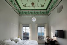 A beautifully appointed guest room at the Efendi Hotel in Acre, Israel features hand-stenciled, Ottoman-era ceilings