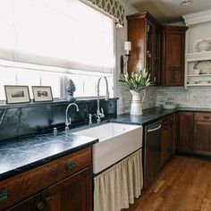 lovely kitchen with cherry cabinets topped with soapstone countertops and soapstone slab backsplash framing skirted farmhouse sink below window dressed in