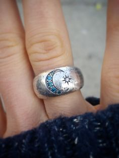 Our Once in a Blue Moon Ring features an engraved Crescent moon of Teal Blue Diamonds and a Brilliant starburst with a shining White Diamond (all VS Quality). This rarity in the sky (the second full moon in a month) has been the basis of myths, legends, and superstitions throughout the world for centuries. This is the perfect ring for the girl with Wanderlust in her Heart and Stars in her Eyes. Handcrafted in Sterling Silver this hearty band has an organic, rustic texture. Measures 11.25mm…