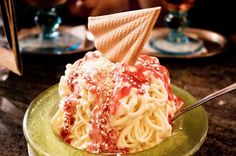 Spaghettieis is an ice cream sundae which you can recreate at home. Spaghetti Eis, once found only in German ice cream parlors, is an easy German specialty with a large fun factor. Vanilla ice cream is pressed through a potato ricer and drizzled with strawberry sauce and white chocolate flakes to simulate noodles, tomato sauce and Parmesan cheese.