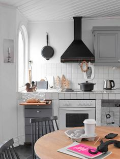 Silje-7; love the black and white kitchen with cabinets in different shades of gray, pops of color and natural light wood