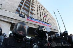 親ロシア派が2都市の行政庁舎を占拠、ウクライナ東部 国際ニュース:AFPBB News   ウクライナ東部ドネツク(Donetsk)で、政府庁舎に侵入し、ロシア国旗と「ドネツク共和国」の国旗とされるものを掲げる親ロシア派の人々(2014年4月6日撮影)。(c)AFP/ALEXANDER KHUDOTEPLY