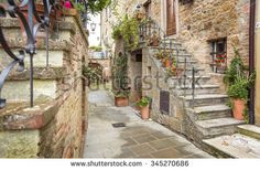 inside in yard of Tuscany city with flowers above the stairs in Italy