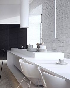 White clean minimal kitchen dining table--love the white painted brick wall against black cabinets