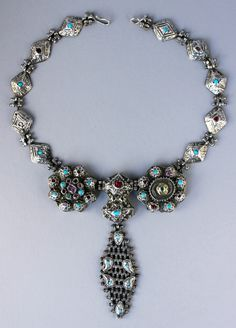 An Armenian necklace in gilt silver with very fine turquoise, rubies, emeralds, and a jade plaque inlaid with high carat gold.  This is a remnant of a larger headdress reworked as a necklace.  From Van, Turkey.  Late Ottoman period, likely 18th century.