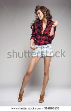 Full-length portrait young sexy woman in jeans shorts, red checked shirt, red lips, high heels shoes. Fashion studio shot. - stock photo