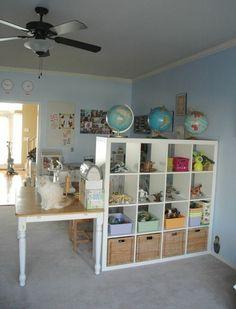 This is a great, useful way to divide playroom space into smaller nooks- a craft area and a play area.