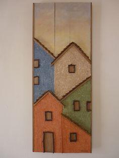 Quadro feito com sobras de madeira de pinus com aplicação de papel machê formando um lindo casario.