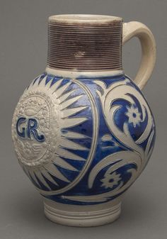 "Jug commemorating King George I (r. 1714–27) or II (r. 1727–60)  Germany; 1714–60  Stoneware  Inscribed ""GR""  Gift of Mr. and Mrs. Dwight P. Lanmon 1992.124  These three vessels were appropriate for serving wine, beer, and concoctions like punch. The William III portrait mug and George I or II jug, initialed for the Latin Georgius Rex, are sturdy salt-glazed stoneware of the type made for several centuries in the Westerwald region of what is now Germany"