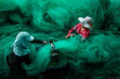Sewing the fishing net Photo by Quang Tran — National Geographic Your Shot
