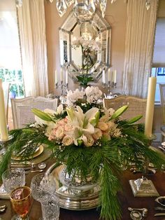 Cut crystal and lots of silver making everything glitter. Lots of greenery with lilies, red tipped roses, and white cyclamen.