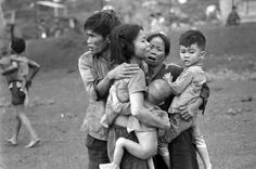 In this June 1965 photo, South Vietnamese civilians, among the few survivors of two days of heavy fighting, huddle together in the aftermath of an attack by government troops to retake the post at Dong Xoai, Vietnam. (Photo by AP Photo/Horst Faas)