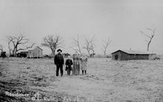 """100.""""Residence of G. L. Rule Feb. 18, 1898. Have lived here since Sept. 1893."""" Family stands in foreground; sod building and cabin in background, Arizona Territory. 48-RST-7B-4"""