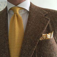 Brown jacket, white shirt, yellow knit tie