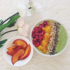 Frozen banana, grape, spinach and matcha smoothie bowl topped with frozen raspberries, mango, buckwheat and chia seeds, with a side of cinnamon coated grilled peaches