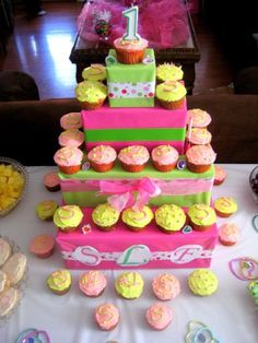 Great way to make a kids birthday cake look big. Wrap different sized boxes  place cupcakes around the sides.