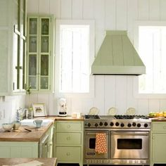 Seaside country cottage kitchen in pale sage green...