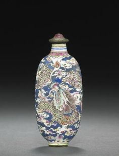 "An enamel on copper ''dragon "" snuff bottle. Probably Imperial, Palace Workshops, Guangzhou, 1720-1750. Very well-hollowed, the elongated ovoid bottle with a spreading neck, thin lip, raised oval foot, painted in enamels on a blue ground with two dynamic dragons amid cloud scrolls to the front and back, one with its mouth wide open, revealing sharp teeth, the other with a raised head and breathing out a flaming pearl. 2 7/8in (7.3cm) high"