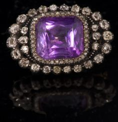 Victorian amethyst and diamond brooch set with rectangular cushion cut amethyst measuring approx 15mm x 13mm surrounded by outer graduated borders of old cut and rose cut diamonds in silver setting on yellow metal closed back setting, 34mm x 22mm.