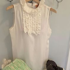 Tory Burch Silk Ruffle Top To die for beautiful Tory Silk Sleeveless Ruffle Top.  Pairs great with jeans for a casual summer look, fabulous work wardrobe staple and fantastic year round layering piece.  Ivory silk with Ruffle collar and chest.  Button detail in the back.  See photos for garment details , size and care instructions.  Bust size is approx 34.5.  Can ship same or next day.  Worn only twice.  Great condition. Tops Blouses