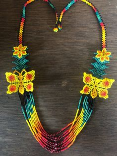 In the Western Sierra Madre Mountains in Mexico, there is a region known as Jalisco where the Wixarika (Huichol) people live. Still holding onto their pre Columbia's ways and ceremonies they continue to create their traditional art and jewelry. These pieces of culture are now Seed Bead Necklace, Seed Bead Jewelry, Bead Jewellery, Seed Beads, Tassel Necklace, Beaded Jewelry, Crochet Bedspread Pattern, Native American Beadwork, Crochet Accessories