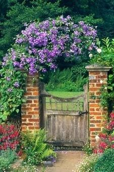 An ordinary gate made special by the brick piers and an arch smothered in clematis.