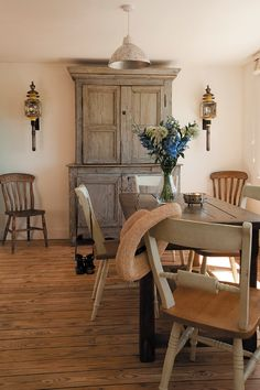 layout: giant armoire centered behind table with extra chairs flanking.