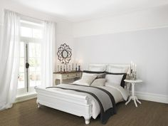 Sophisticated pale grey bedroom painted with Crown matt emulsion in Seldom Seen. White picture rails.