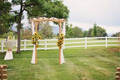 Wooden arch for rustic wedding ceremony draped with white fabric and sunflowers {Alison D. Photography}