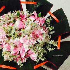 ドラセナの器の中にお花が入っているイメージで、コンカーブという覗き込むタイプのブーケを作りました。アクセントにロールリボンを通してみました。