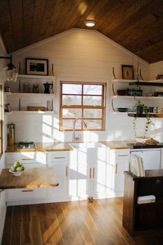 The kitchen has open shelving, custom steel brackets, a farmhouse sink, and butcher block countertops.
